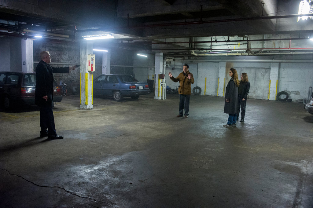 Stan points a gun at Philip, Elizabeth and Paige in a parking garage