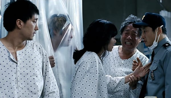 Gang-du and the other members of his family are in hospital gowns, talking with a securtiy gaurd.