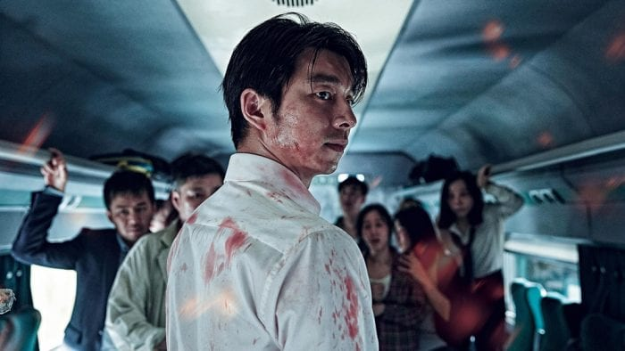 main character seok-woo looking behind him, covered in blood. passengers of the train stare in the same direction behind him.