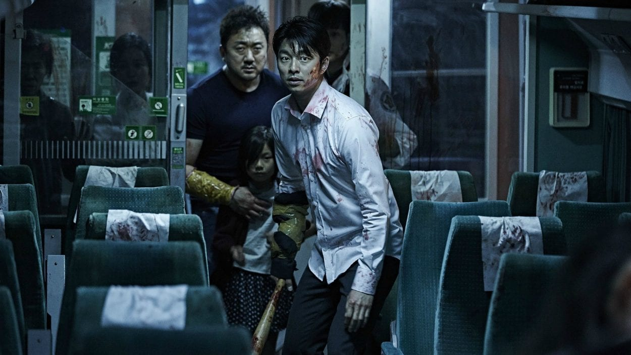 main characters seok-woo, su-an, and sang-hwa carefully walking through a train car, with sang-hwa carrying a bat