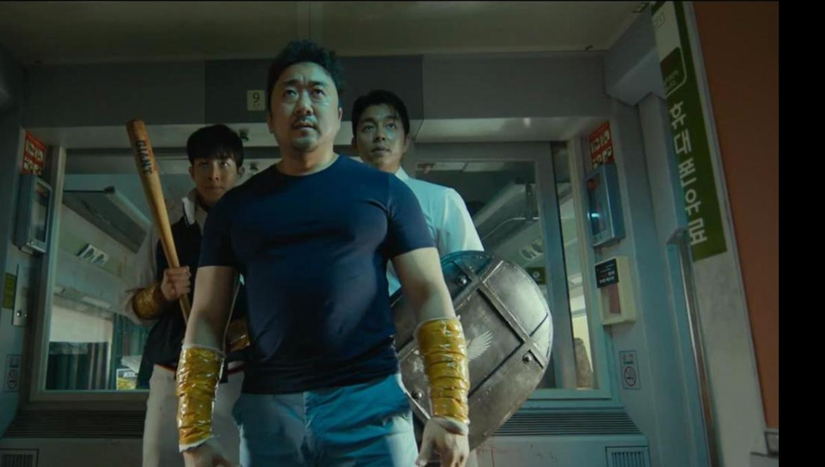 main characters sang-hwa, seok-woo and yong-guk carrying weapons, preparing to fight on the train