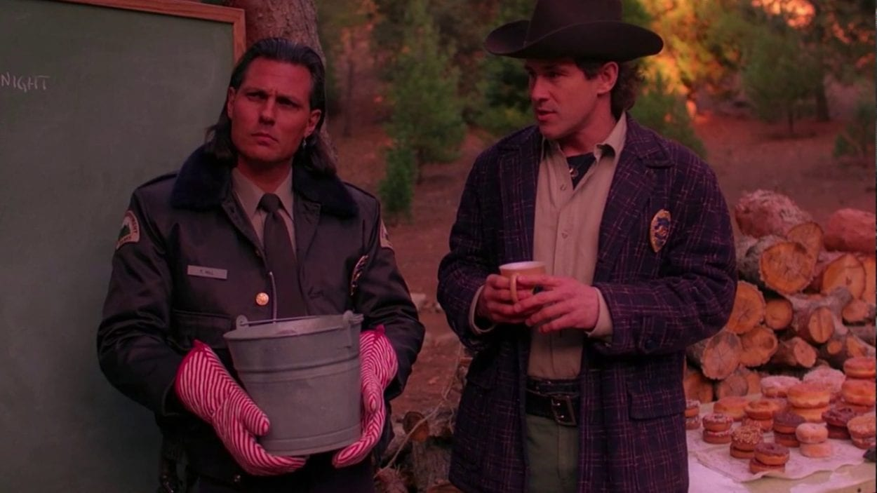Deputy Hawk holds a pot while wearing oven mitts and Sheriff Truman holds a cup of coffee while standing next to a chalkboard in the forest.
