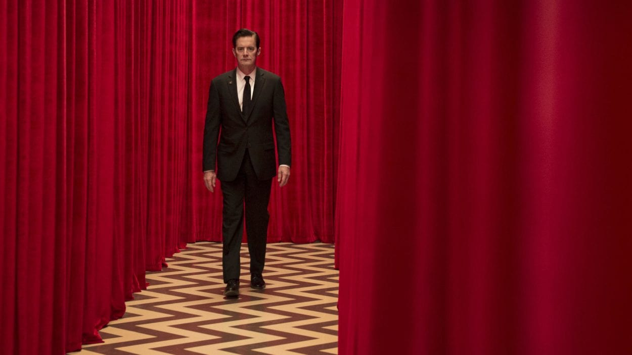 Dale Cooper walks against the red cutrtains of the Red Room