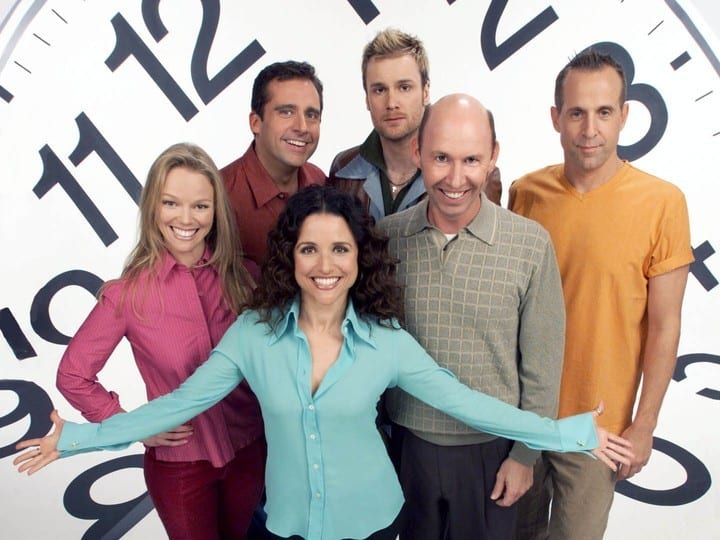 The cast of Watching Ellie stands in front of a large clock