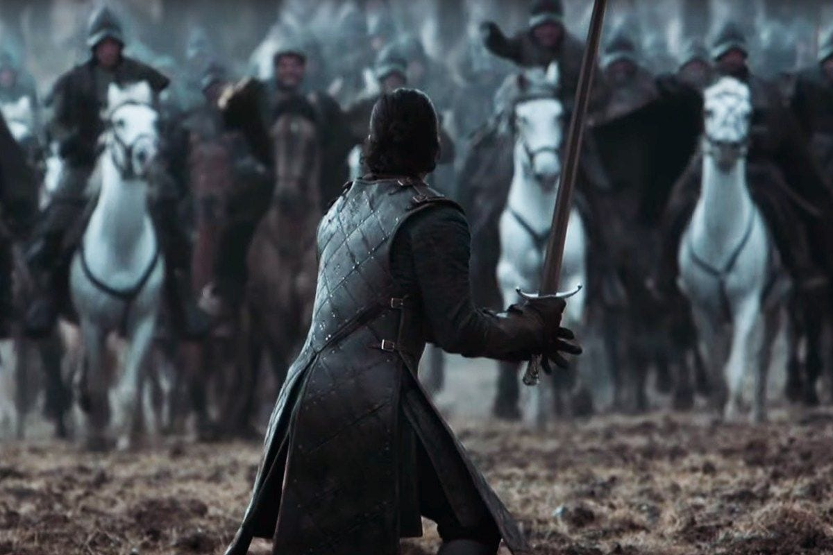 Jon Snow stands with his sword drawn waiting for the oncoming cavalry