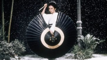 Yuki stands behind an umbrella she uses as a shield and holds her katana high