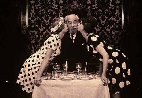 Marie I and Marie II each kiss a cheek of an old man in parallel polka dot dresses