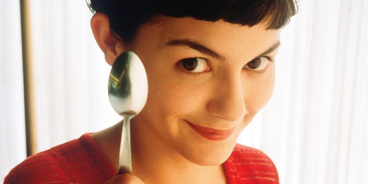 Amelie looking at the camera with a small smile while holding a spoon upwards and straight