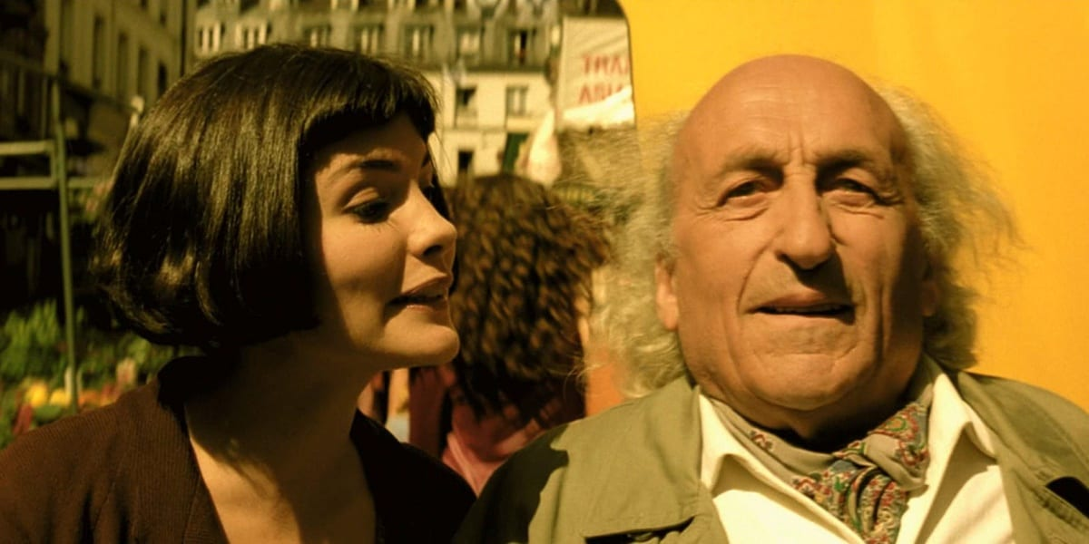 Amelie looking at the man and talking to him, the man staring straight ahead in wonder, yellow building behind them and a woman with her back to them in the background between Amelie and the man