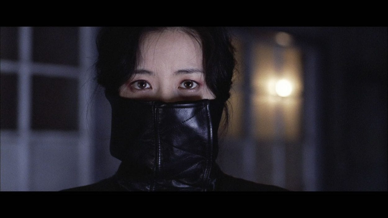 CU of Geum-ja with her high leather collar covering half of her face