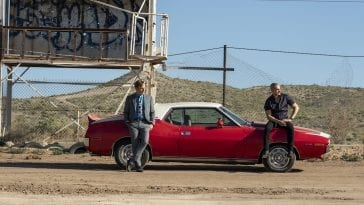 Jimmy and Nacho lean against Nacho's car in the desert waiting for Lalo to arrive