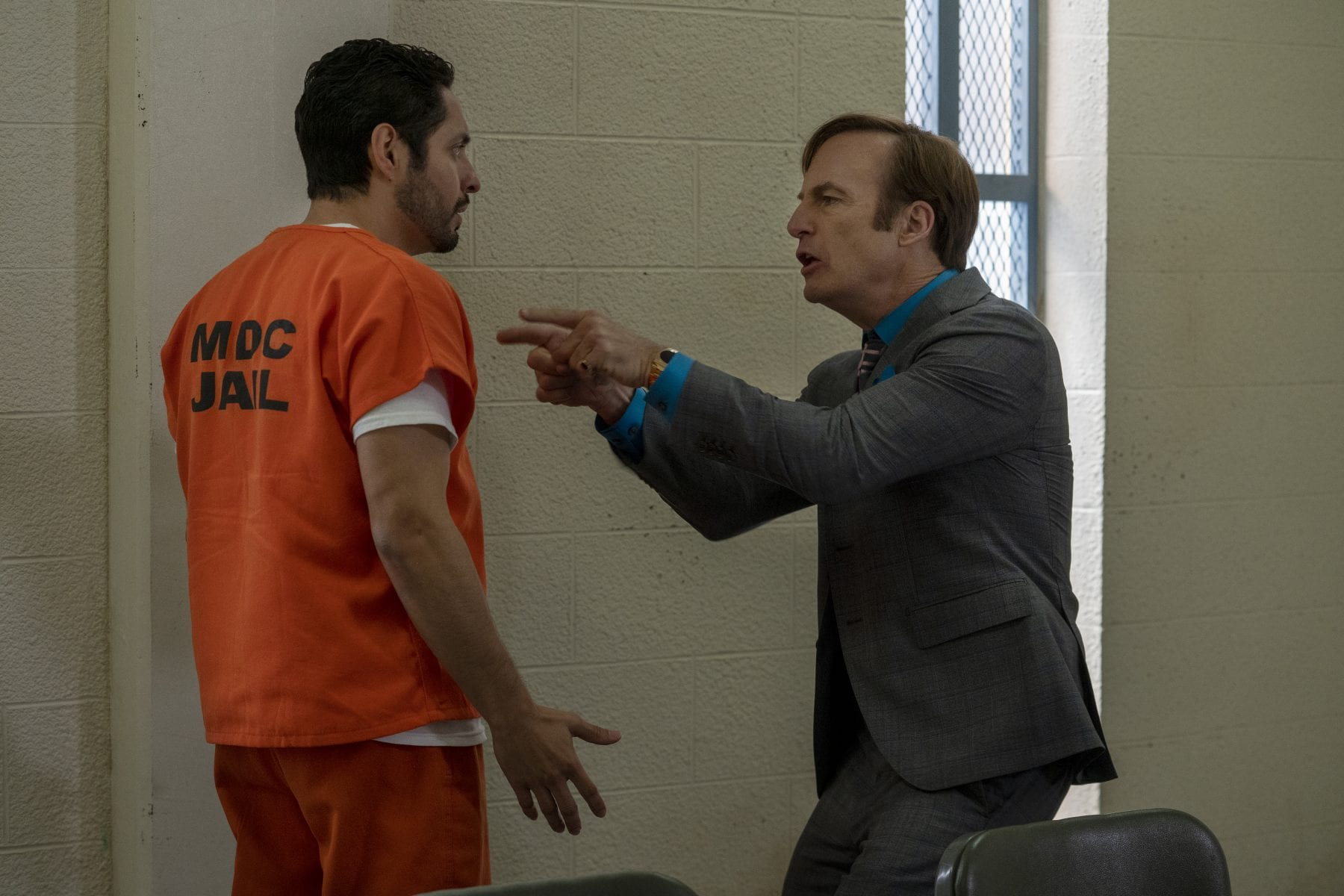 Jimmy points at Domingo wearing an orange prison jumpsuit in the interrogation room