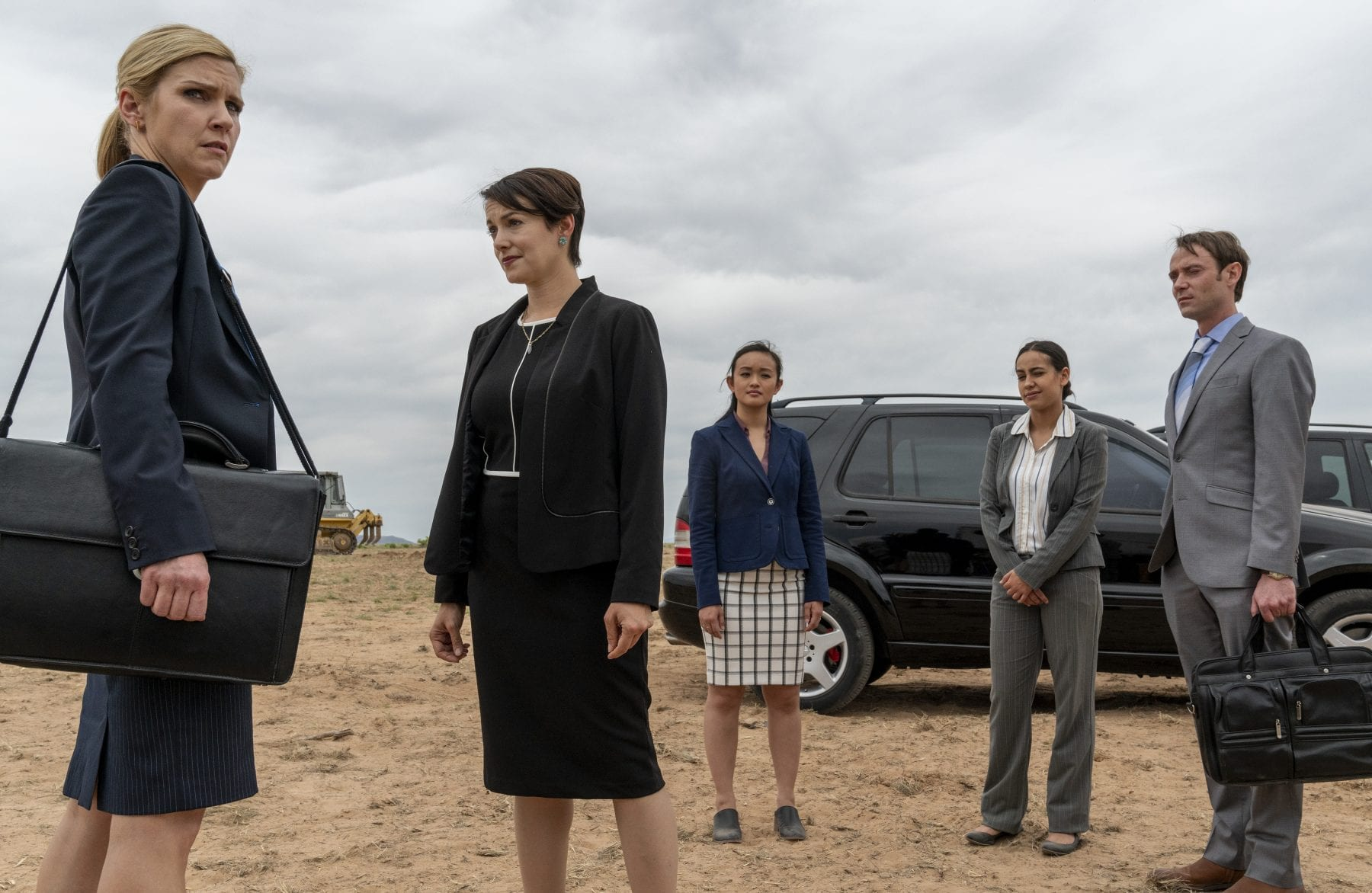 Kim, Paige, and three associates stand in front of a black SUV at the Tucumcari build site