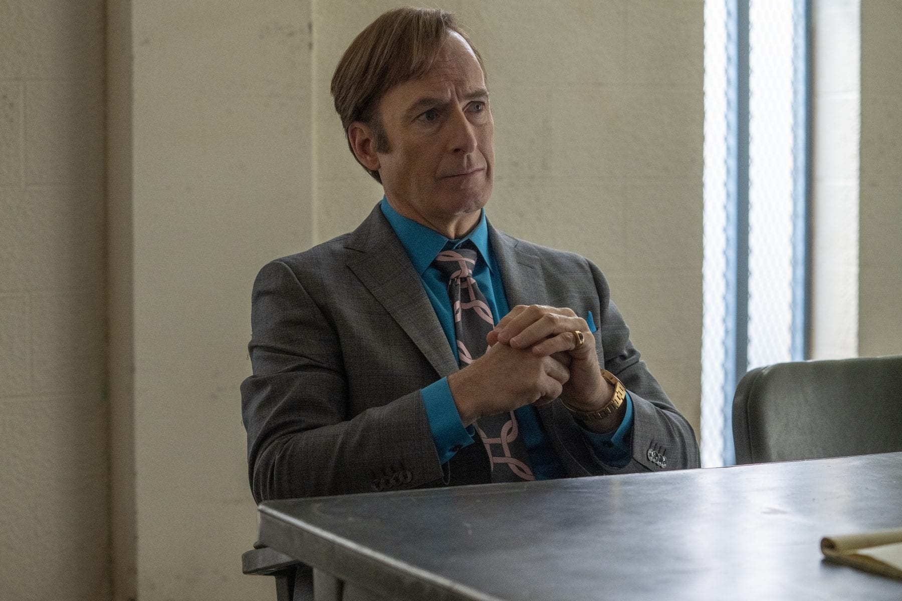 Jimmy sits at the table in the interrogation room practicing law as Saul Goodman