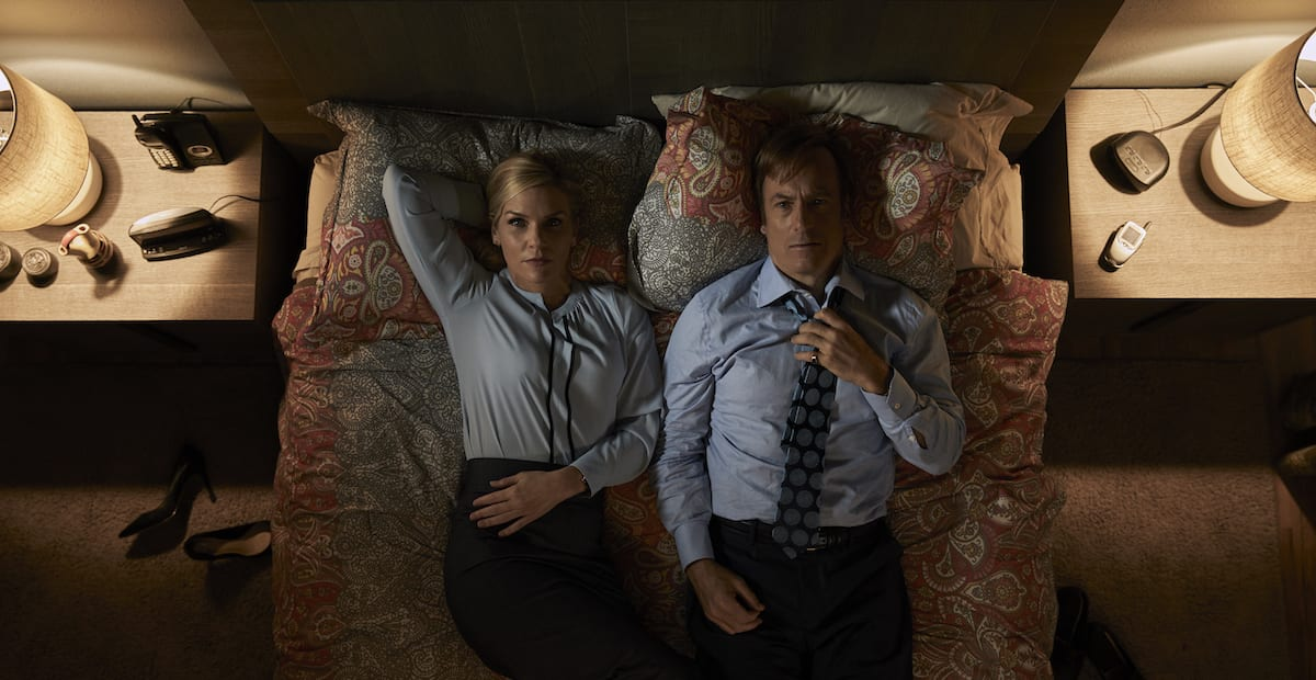 Aerial shot of Jimmy and Kim laying on their bed in their work clothes