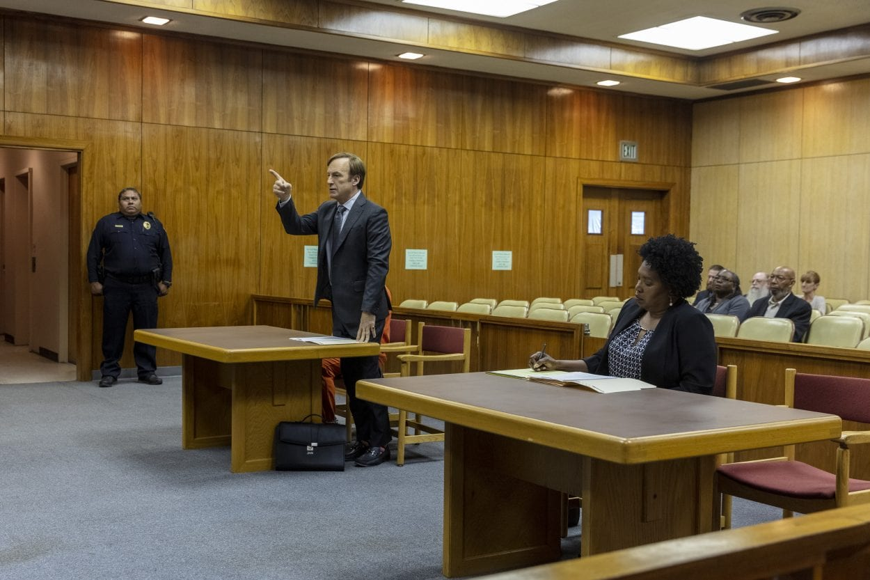 Jimmy stands up and points at the judge as the prosecutor takes notes