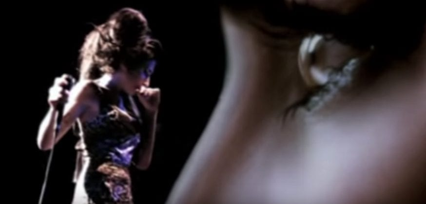 "Amy Winehouse look down while performing in the ""Love is a Losing Game"" music video"