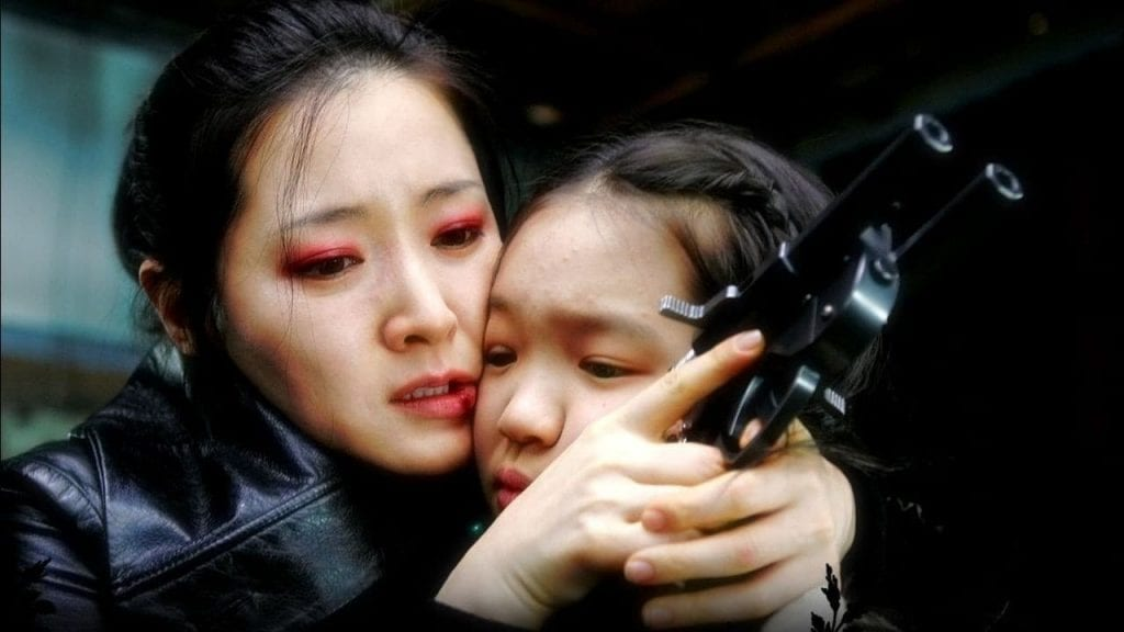 Geum-ja hugs her daughter whilst holding her custom gun