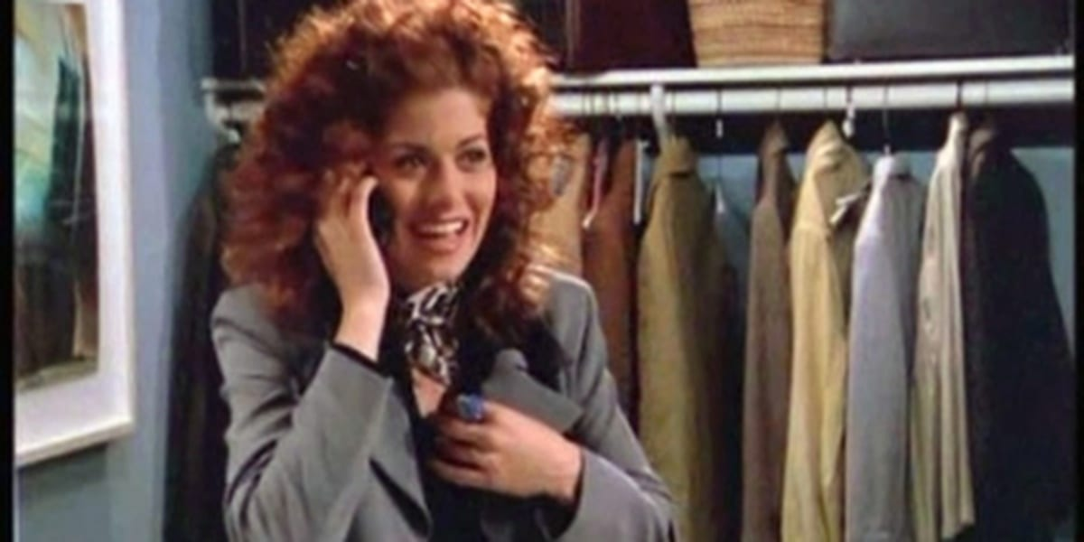 Grace on the phone smiling while hiding in a coat closet in Will and Grace