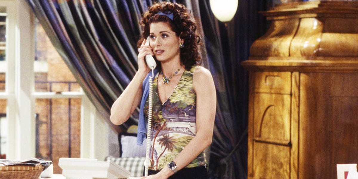 Grace looking hopeful while talking on the phone, holding it to her ear while in her office in Will and Grace