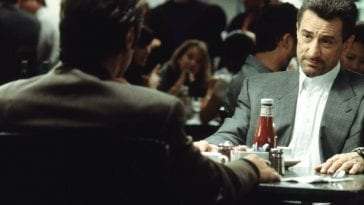 Neil McCauley looks at Vincent Hanna at a dinner table in a crowded restaurant
