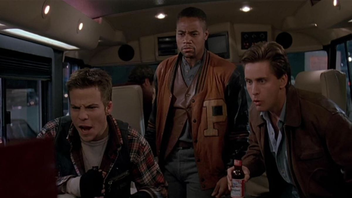 Three friends enjoy a boxing match on the TV in an RV at the start of Judgement Night