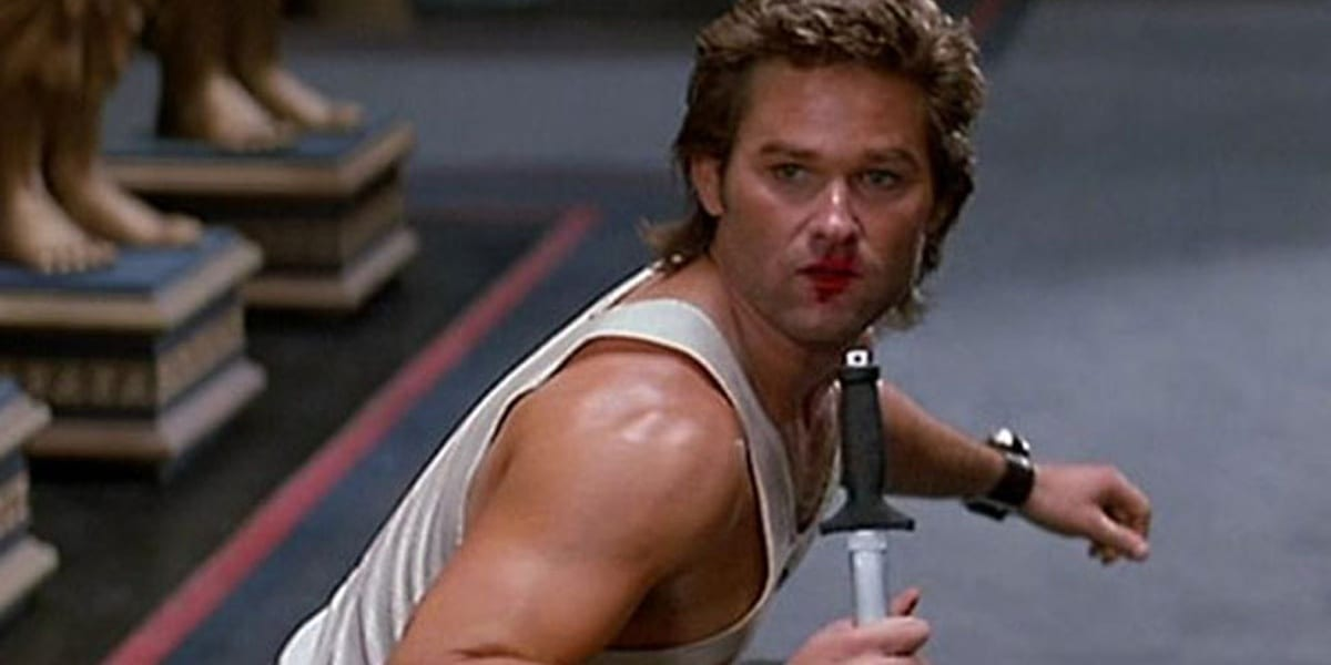 Kurt Russell as Jack Burton in Big Trouble in Little China looking behind him with lipstick on his face and a knife pointing downward in his hand