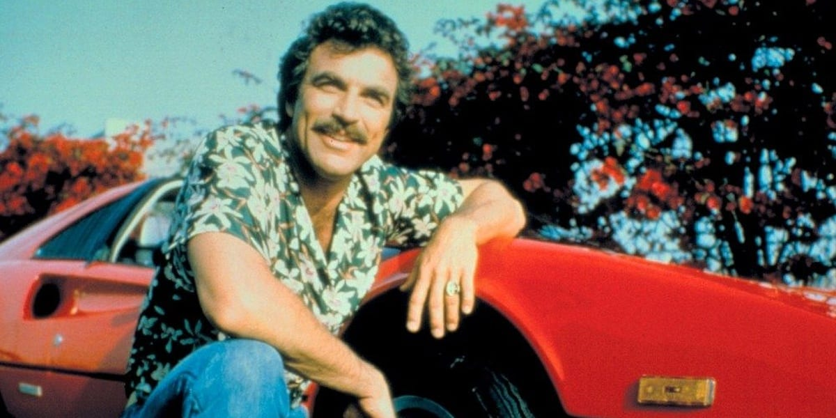 Tom Selleck kneeling to the side of a red Ferrari, arm on the hood, looking ahead with a smile