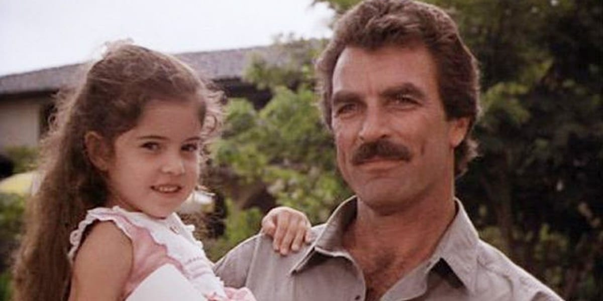 Magnum smiling while holding onto his daughter Lily, who smiles directly at the camera
