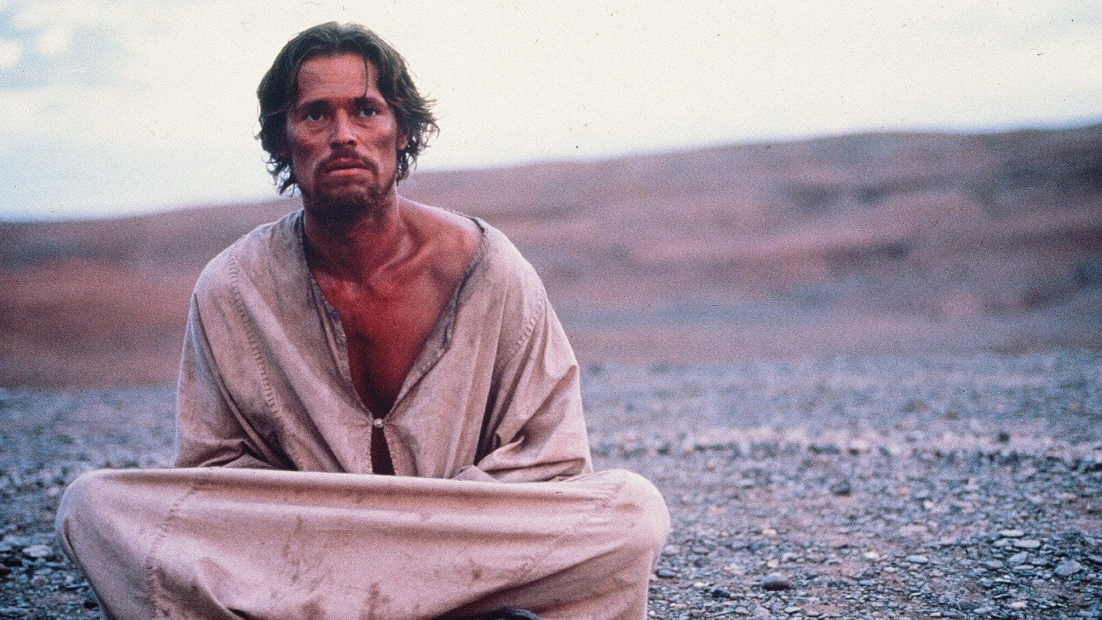 Jesus, looking haggard, sits alone in the desert