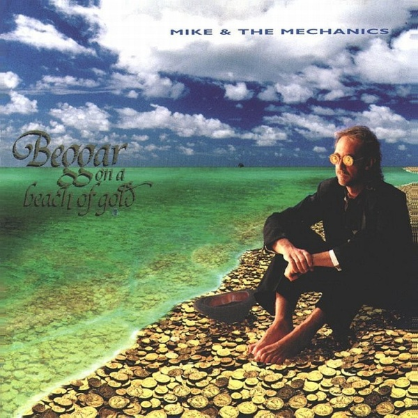 A man in black sits on the beach shoeless. The sky is blue with many white clouds.