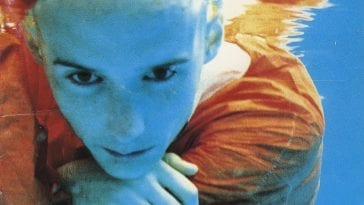 Moby is under water, pensively grabbing his orange shirt while he is lit in blue.