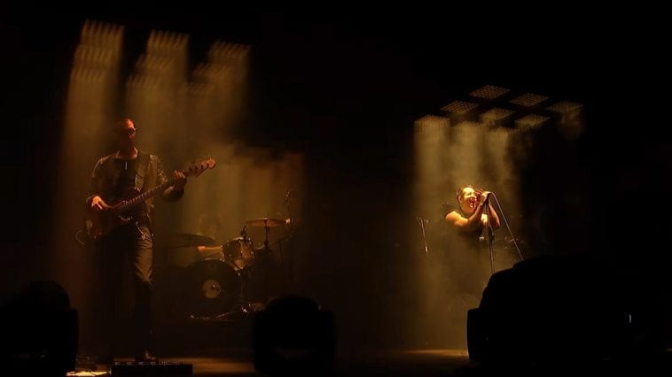 Nine Inch Nails performs live on a dark stage
