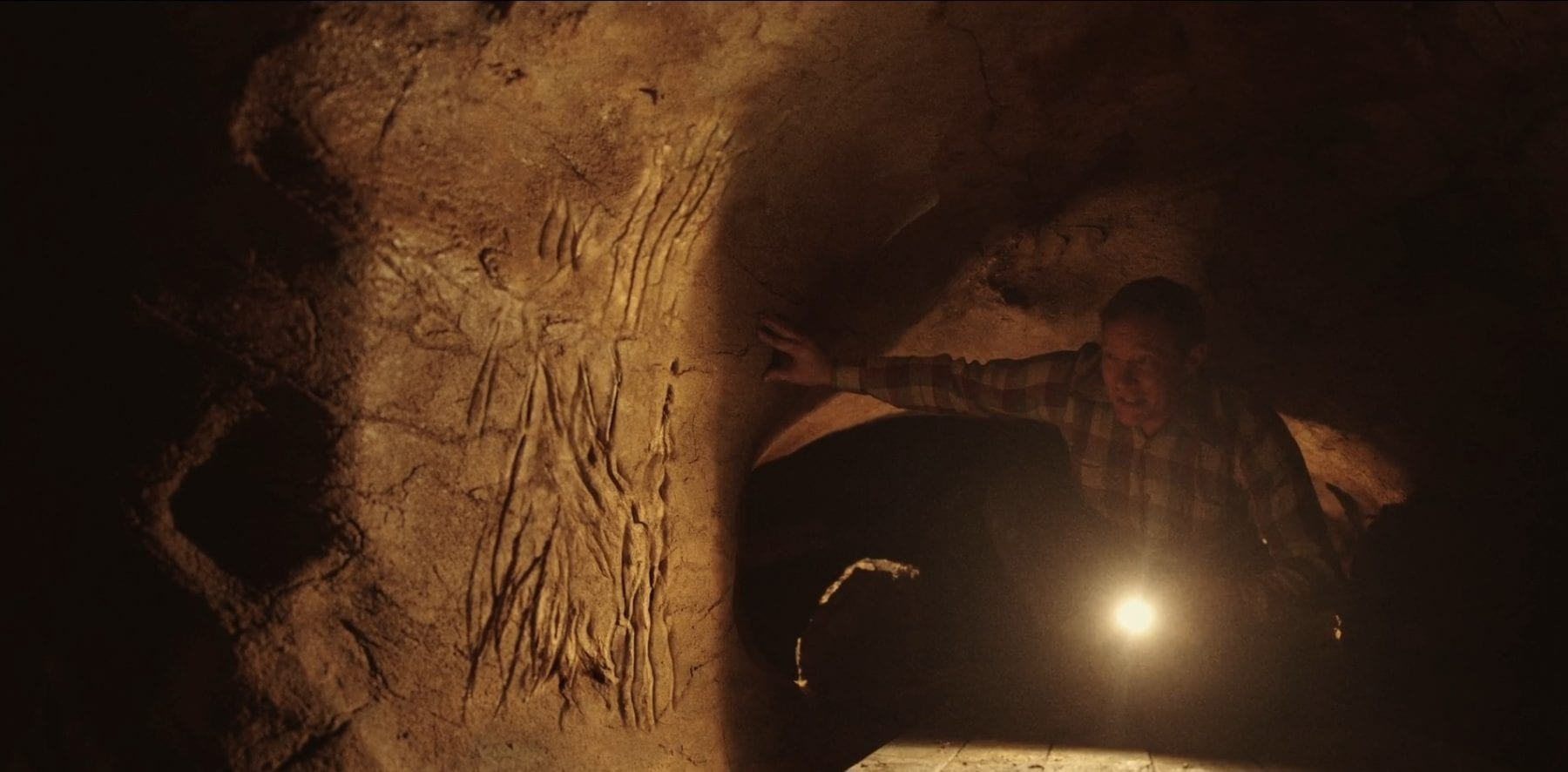 Emmitt Weaver holding a flashlight in the cave, with scratches on the cave wall