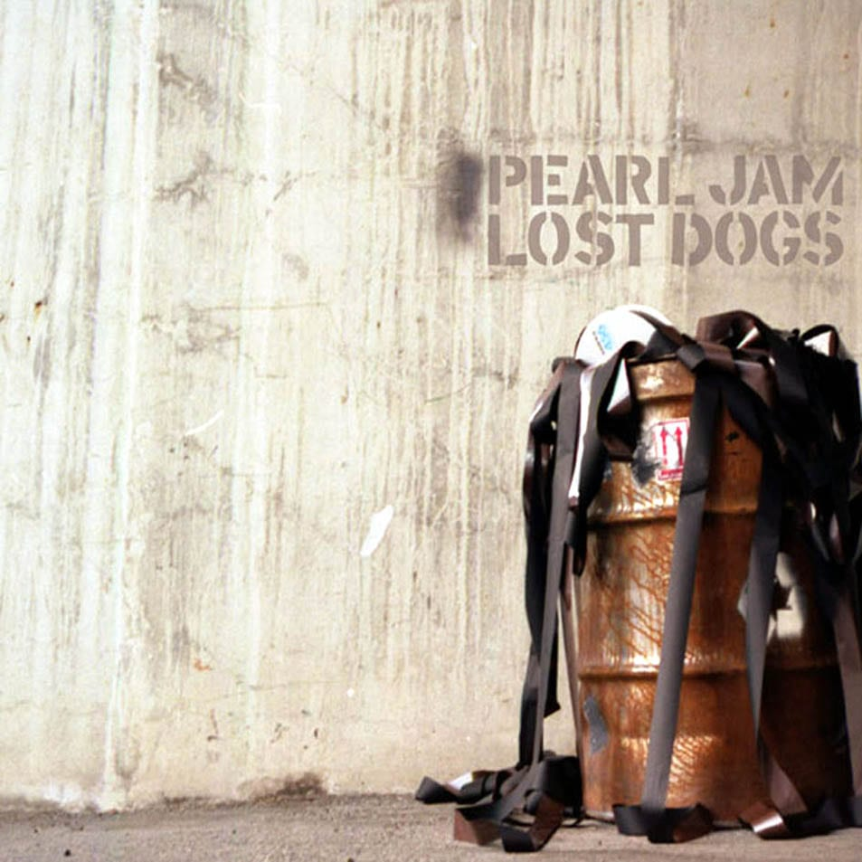"A gray concrete wall with ""Pearl Jam Lost Dogs"" appearing to be etched on it, with a brown barrel below it to the right."