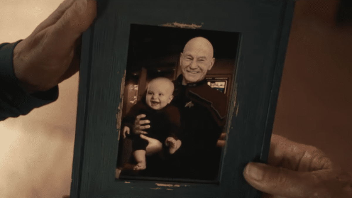 Picard S1E7 - A hand holds a photograph of Picard holding a baby on his lap