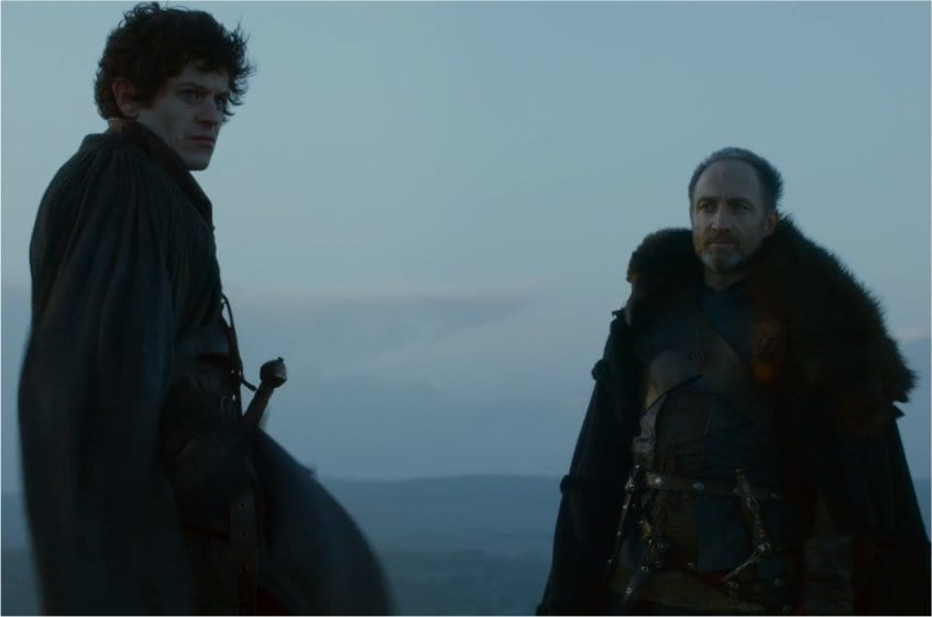 Ramsay and Roose Bolton stand across from each other on a the top of a mountain.