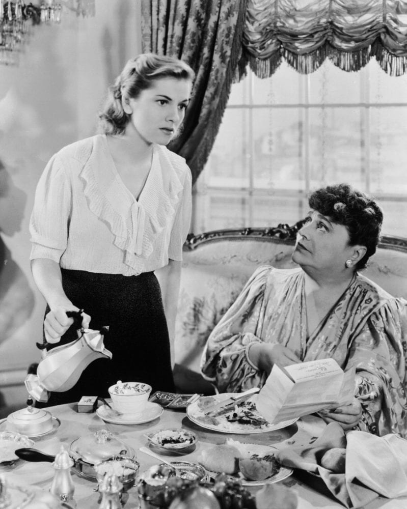 The second Mrs. de Winter pours tea for her employer, the wealthy Edythe Van Hopper.
