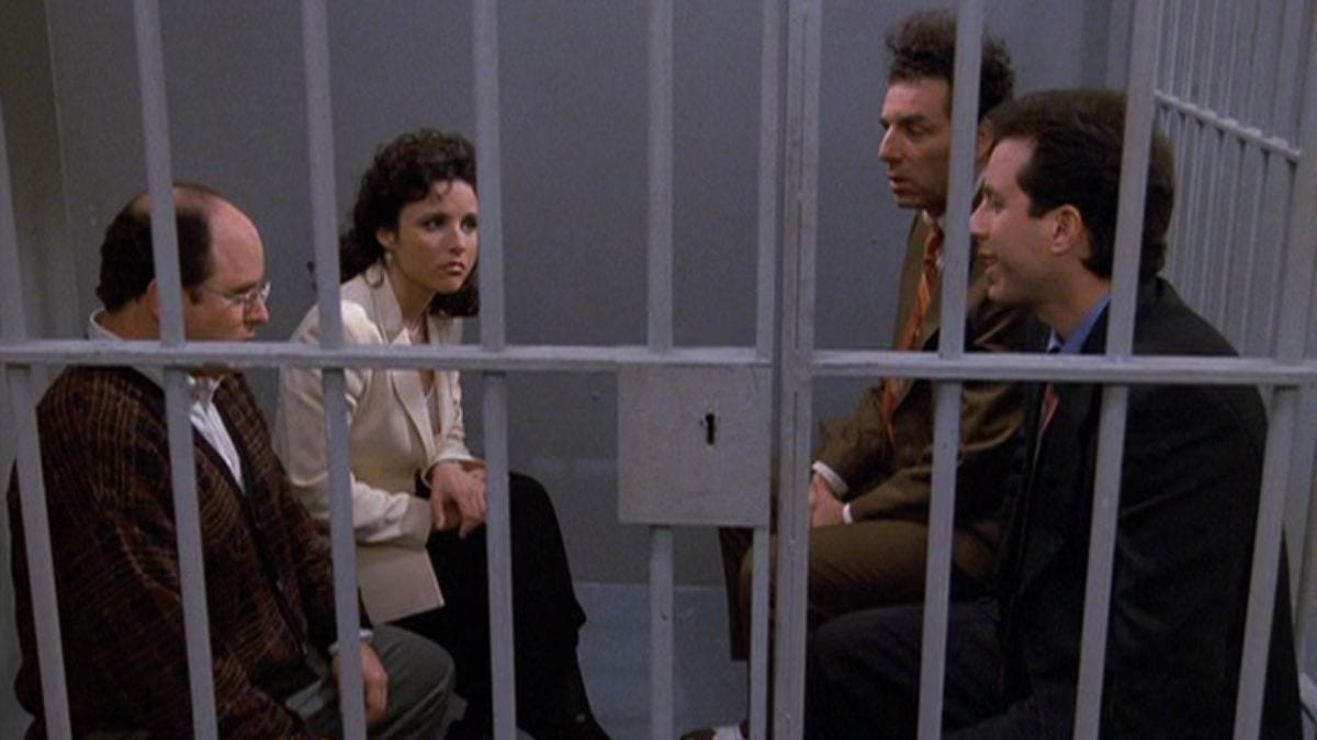 George, Elaine, Kramer, and Jerry sit behind bars in a jail cell