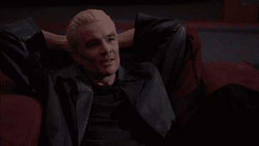 Spike lounges in a chair in Angel's office