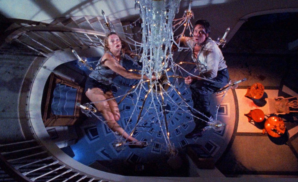 Barbara and Oliver hang dangerously on an insecure chandelier
