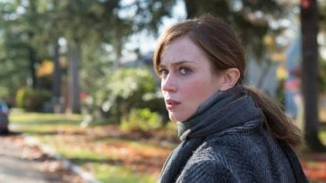 Emily Blunt in The Girl on the Train looking behind her in concern with trees in the sunny background