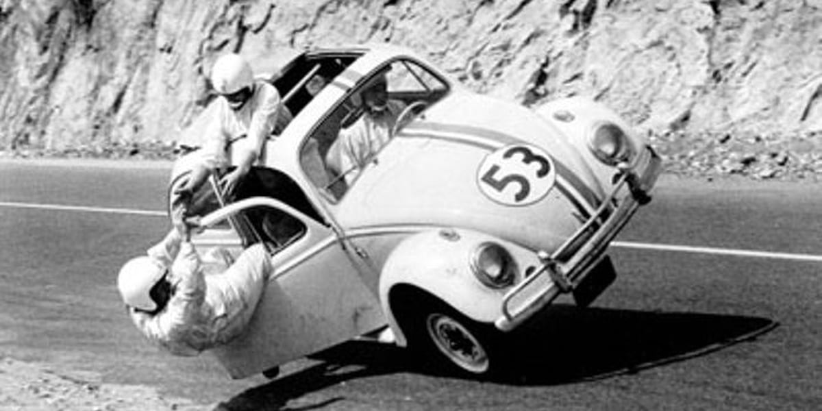 The Love Bug black and white photo of Herbie on two wheels with Michele Lee holding onto Buddy Hackett who's hanging outside the door while Jim drives