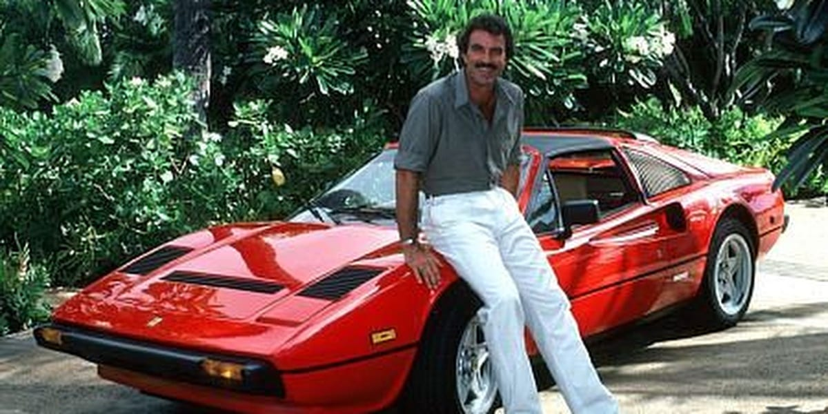 Tom Selleck sitting on Ferrari hood wearing green shirt and white pants smiling at the camera