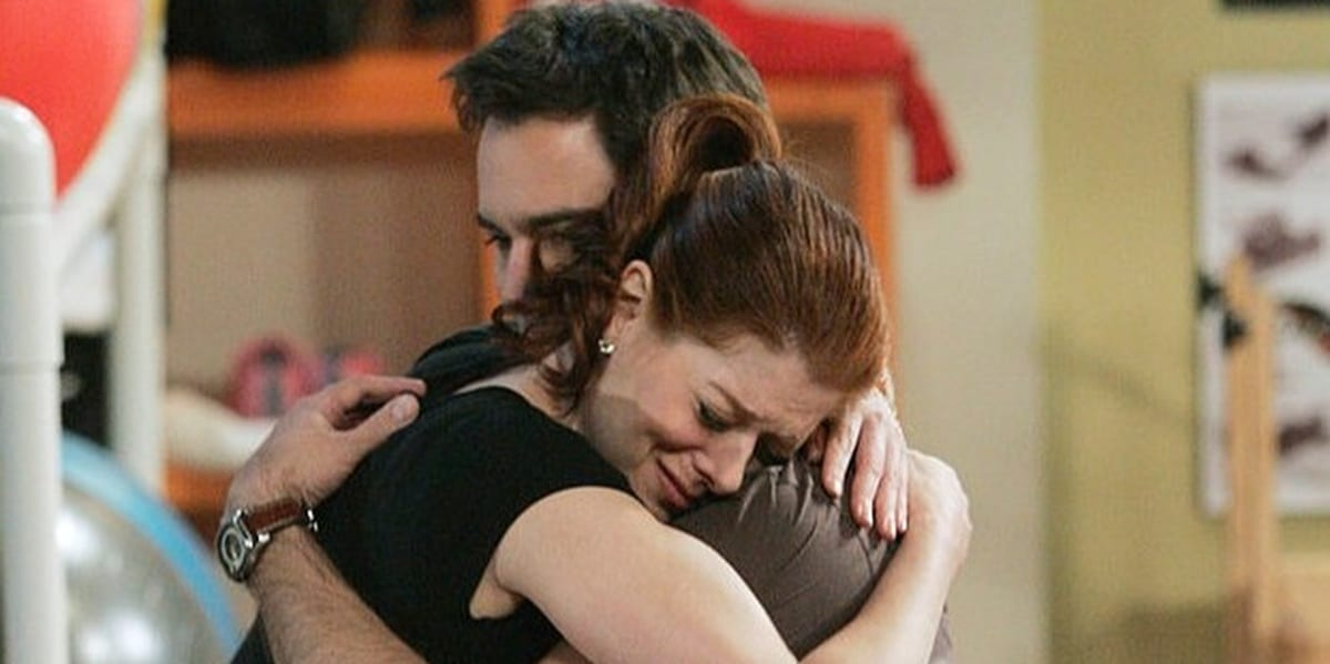 Will and Grace hugging, Grace looking sad, eyes closed, while Will comforts her