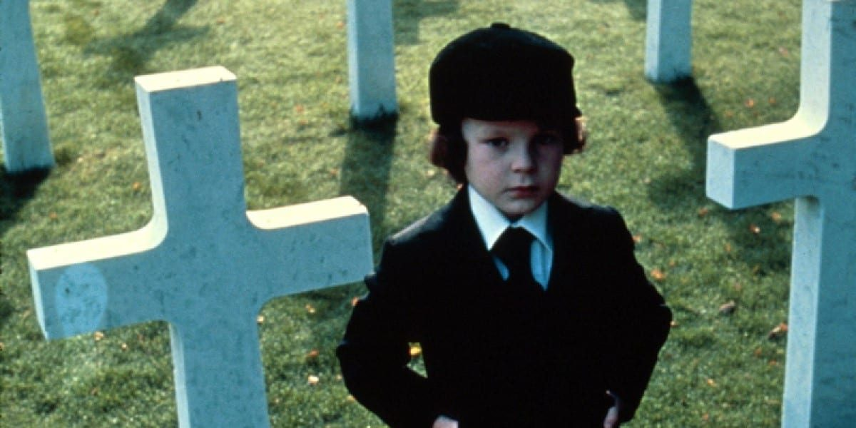 Young Damien standing next to uniform white crosses in a cemetery.