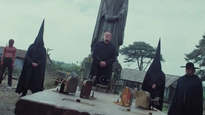 Five figures stand around a block with antiquated machinery in front of a monument. One man is shirtless and bloody, the other men wear all black and two are hooded.