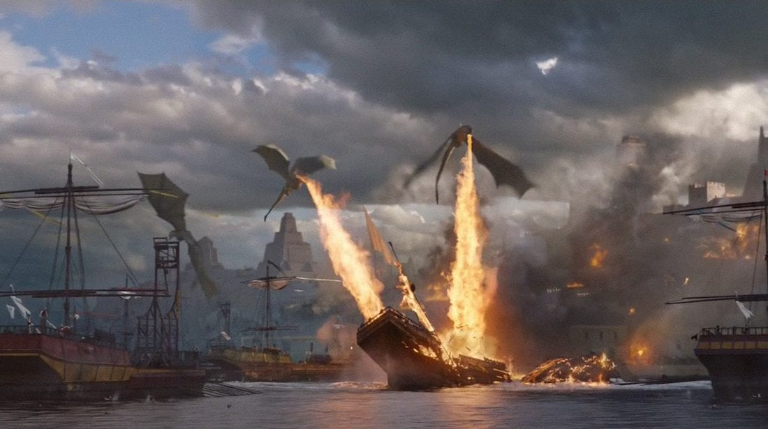 Daenerys' dragons fly above a fleet of ships, setting them on fire as they fly by.