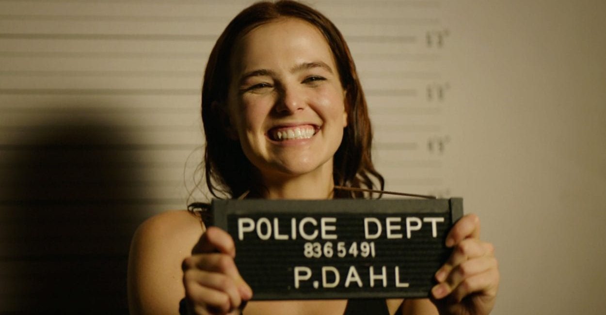 Zoey Dutch as Peg holds up a police sign and grins while getting her mugshot taken