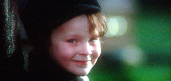 Close-up of Damien's smiling face, while outside at the cemetery.